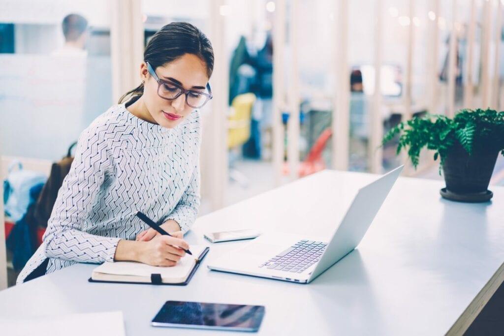 Programy do pisania - kobieta pisze w notesie mimo że ma laptopa